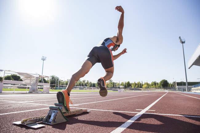 Runner on tartan track starting at stadium — Stock Photo