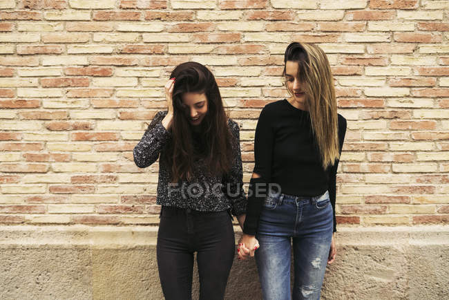 Two women holding hands in front of brick wall looking down — Stock Photo