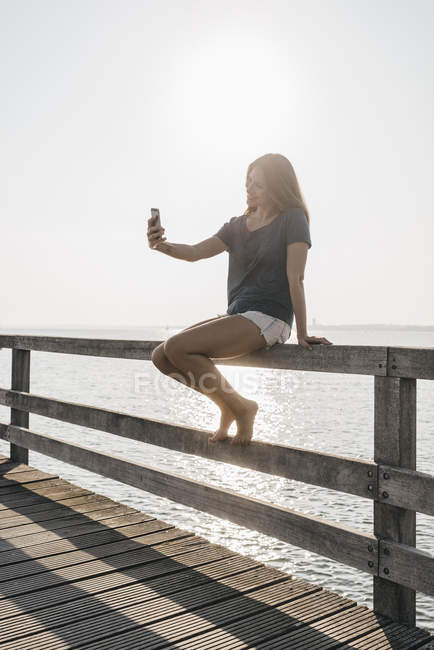 Young woman sitting on jetty at backlight taking selfie with cell phone — Stock Photo