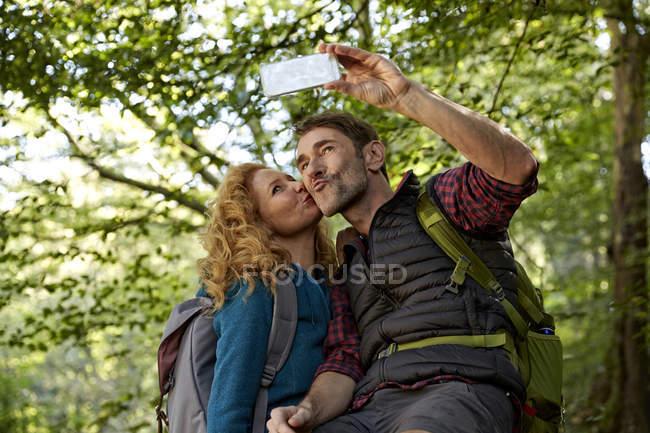 Пешая пара делает селфи со смартфоном в лесу — стоковое фото