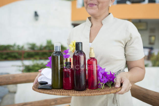 Massage therapist holding a tray with oil, lotion and towels — Stock Photo
