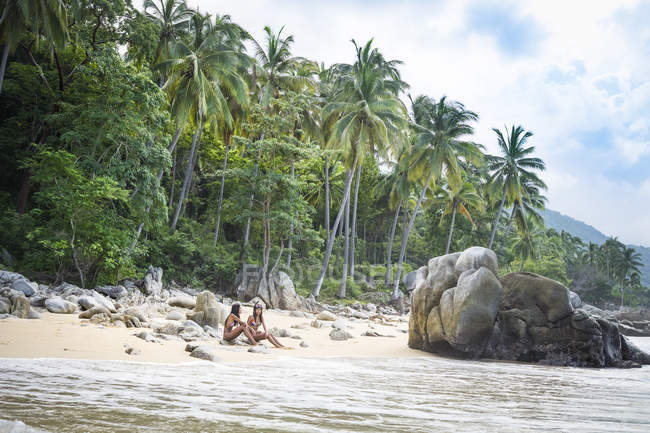 México, Puerto Vallarta, Bahía de Banderas, dos mujeres en playa tropical - foto de stock