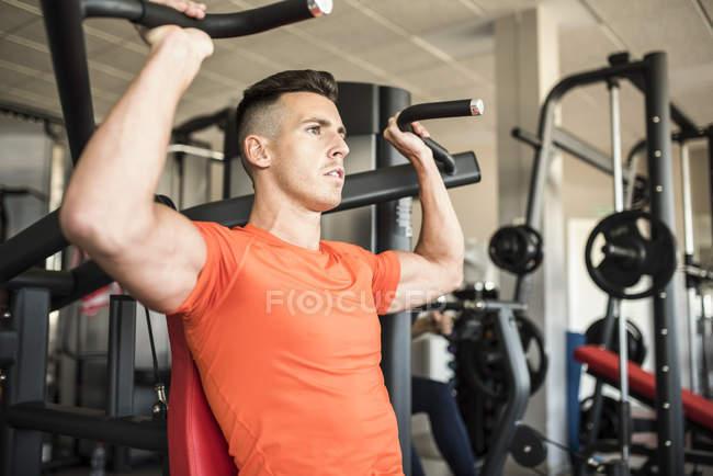 Handsome caucasian man exercising in gym — Stock Photo