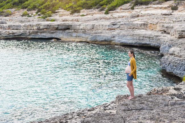 Беременная женщина стоит на скалистом берегу у моря — стоковое фото