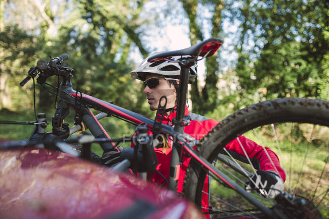 Mountain biker preparing bicycle to put in a car — Stock Photo