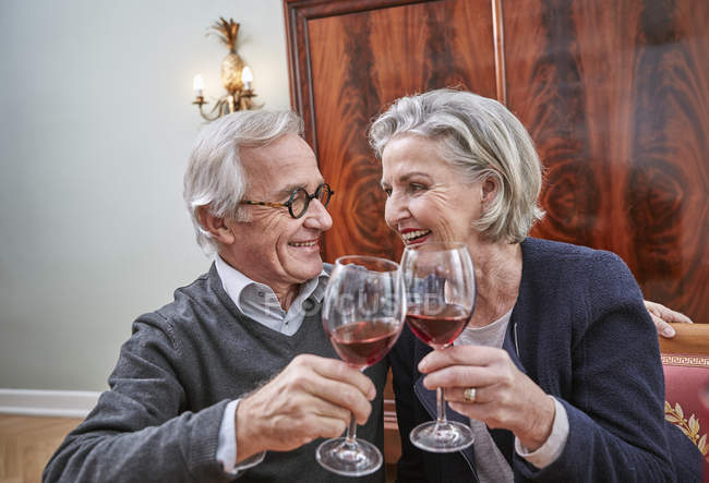 Smiling senior couple clinking red wine glasses — Stock Photo