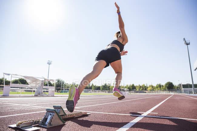 Женщины бегун на треке тартан начиная на стадионе — стоковое фото