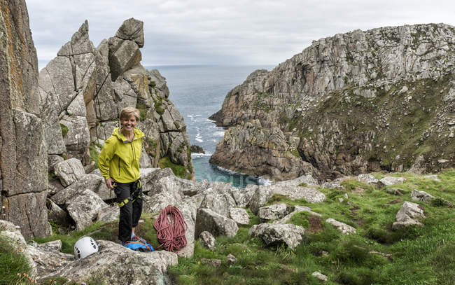 Великобритания, Корнуолл, улыбающаяся женщина готовится к восхождению по маршруту Коммандо Ридж — стоковое фото