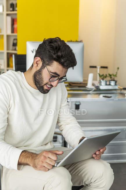 Joven con portátil sentado en una oficina moderna - foto de stock