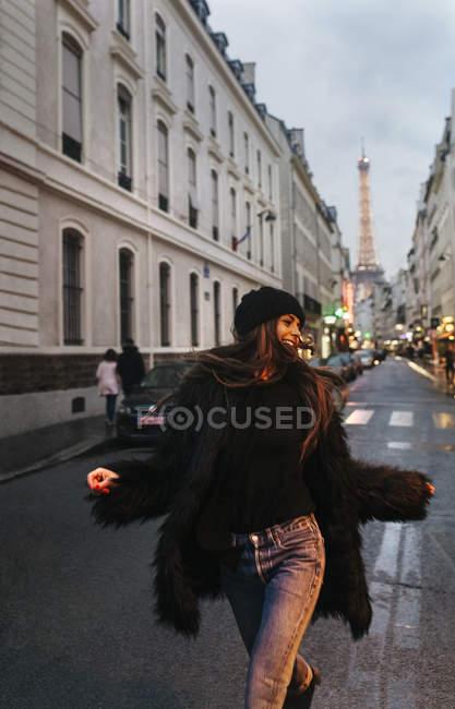Франция, Париж, молодая женщина на улице с Эйфелевой башней на заднем плане — стоковое фото
