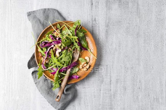 Salat mit Rotkohl, Rucola, Einkornweizen und verschiedenen Nüssen auf Holzteller — Stockfoto