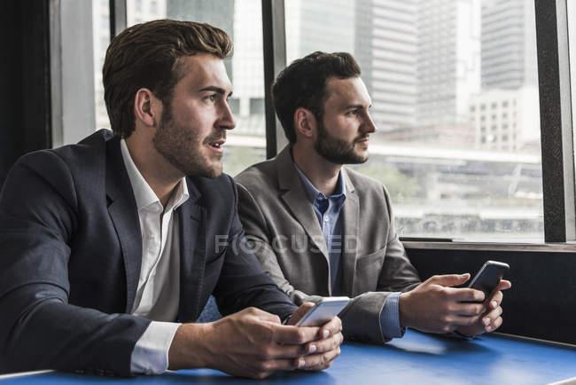 Deux hommes d'affaires avec des téléphones portables sur le pont passager d'un ferry — Photo de stock