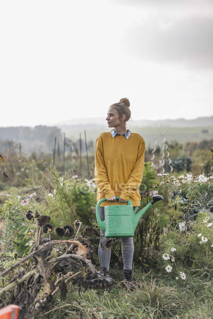 Young woman holding watering can in cottage garden — Stock Photo
