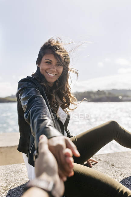 Portrait of smiling young woman with brown hair holding hands on waterfront — Stock Photo