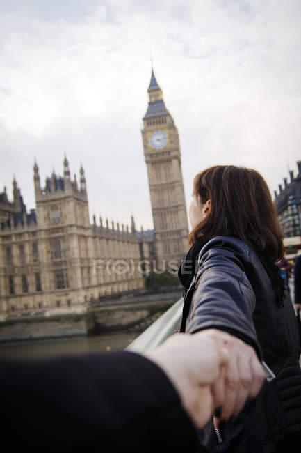 UK, London, woman pulling friend towards Big Ben — Stock Photo