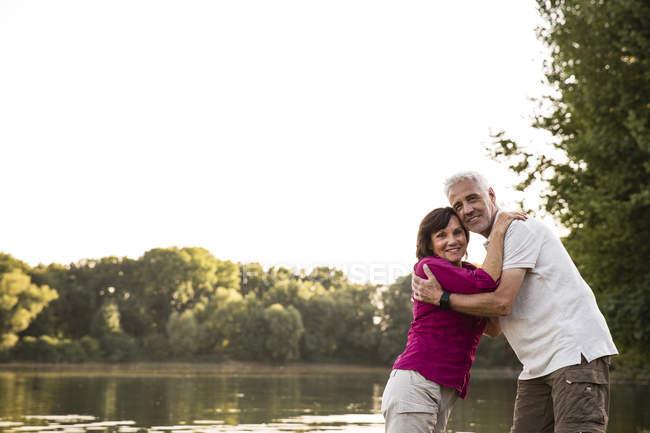 Улыбающаяся пожилая пара, обнимающая озеро — стоковое фото