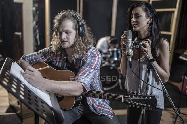 Singer and guitarist in musical recording studio — Stock Photo