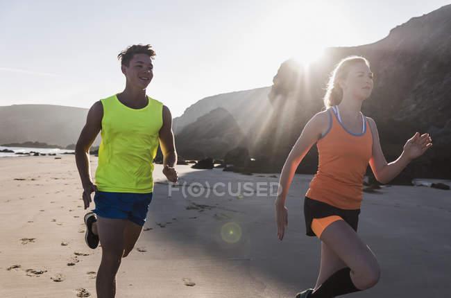 Молодая пара бегает по пляжу, Франции, полуострову Крозон — стоковое фото