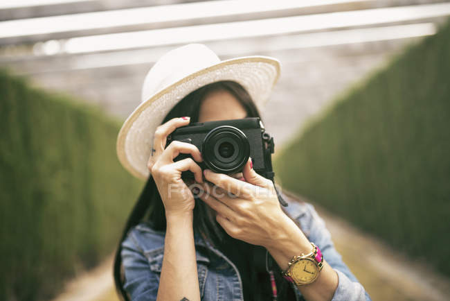 Young woman wearing hat taking picture — Stock Photo