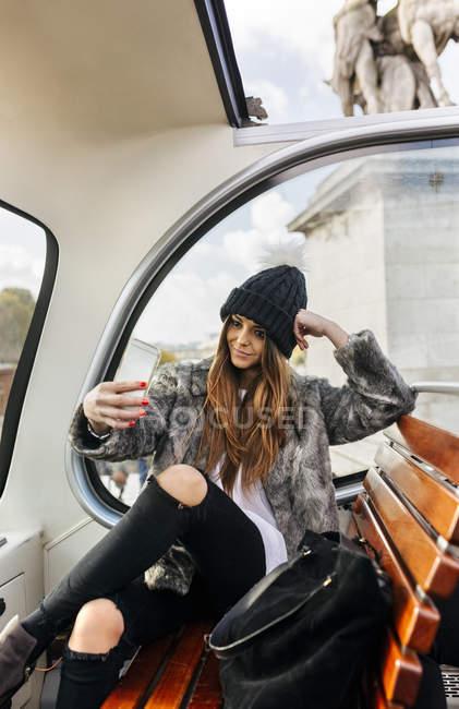 Smiling woman taking a selfie on a tour bus — Stock Photo