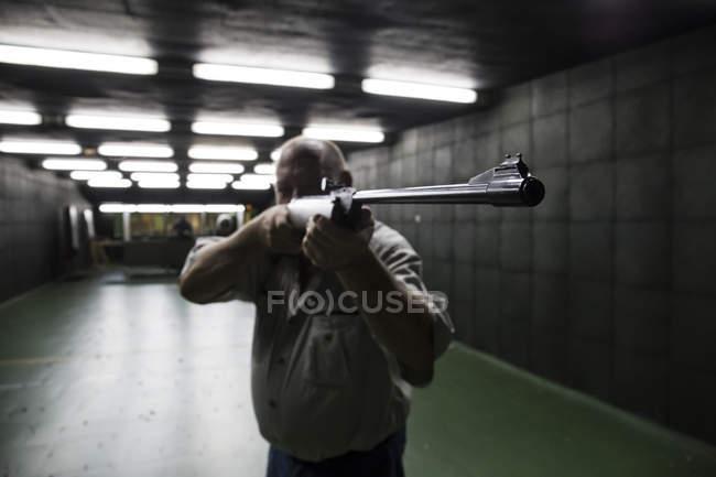 Homem com o objetivo com uma carabina em um campo de tiro indoor — Fotografia de Stock