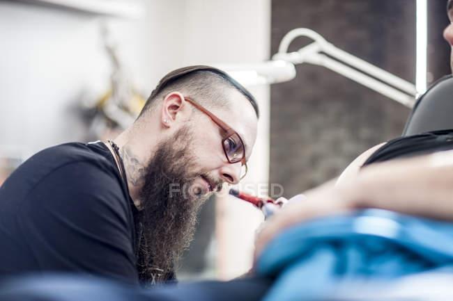Concentré de tatoueur travaillant en studio — Photo de stock