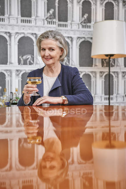 Portrait of senior woman drinking glass of champagne — Stock Photo