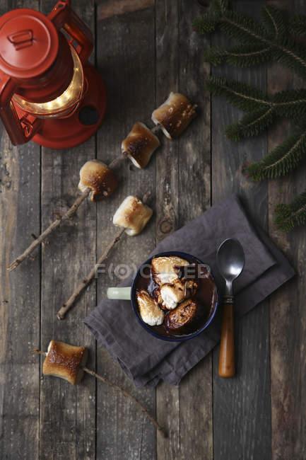 Chocolate caliente con malvaviscos tostados al fuego sobre mesa de madera - foto de stock