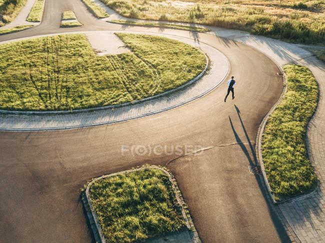Uomo d'affari fiducioso che corre in rotonda sotto il sole — Foto stock