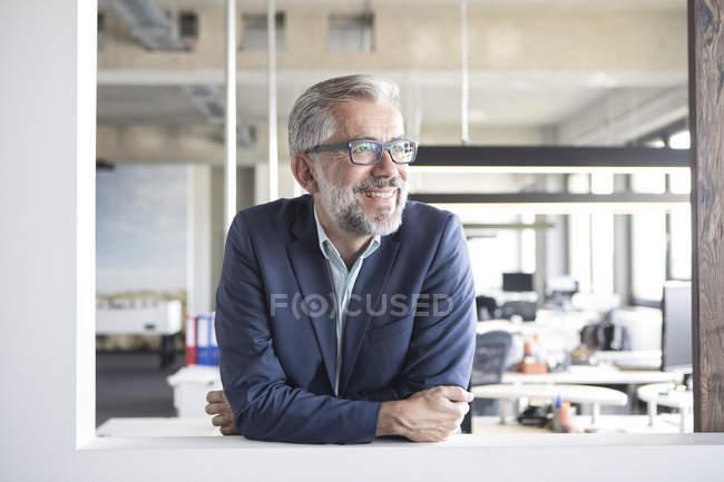Усміхаючись бізнесмен дивиться вбік в офісі — стокове фото