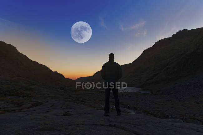España, Sierra de Gredos, silueta del hombre mirando a la luna llena - foto de stock