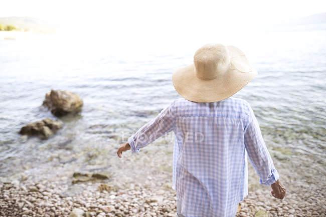 Задний вид веселой пожилой женщины, стоящей на пляже — стоковое фото
