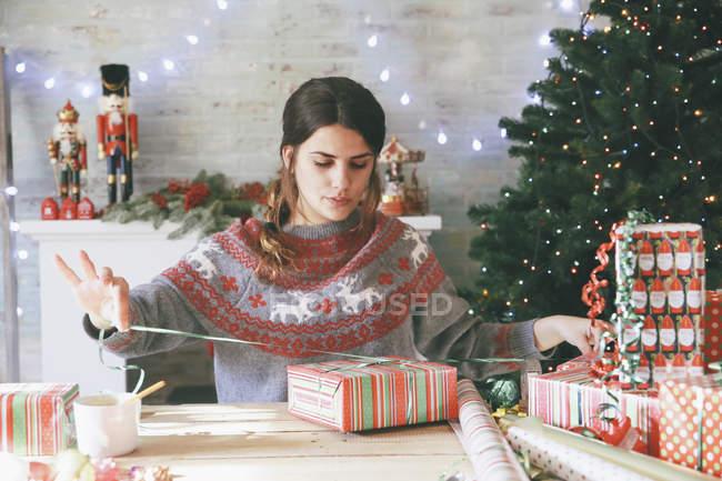 Mulher embrulhar prendas de Natal em casa — Fotografia de Stock