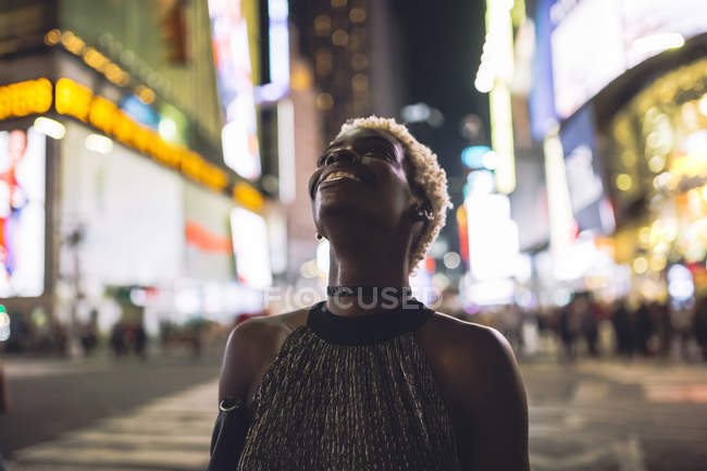 Smiling young woman walking on Times Square at night, New York City, USA — Stock Photo