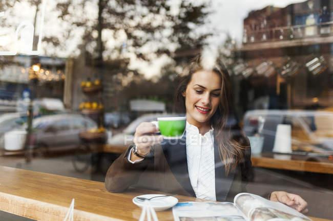 Lächelnde junge Frau in einem Café eine Zeitschrift liest — Stockfoto