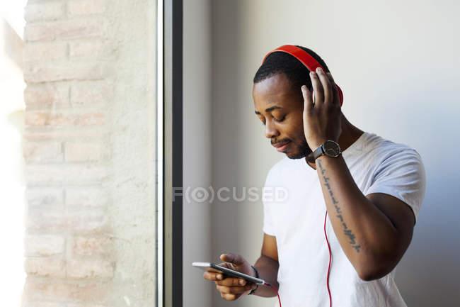 Giovane con cuffie e smartphone alla finestra — Foto stock