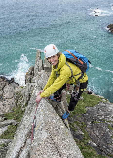 UK, Cornwall, smiling woman climbing on Commando Ridge — Stock Photo