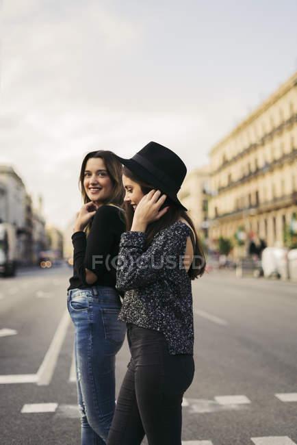 Two best friends crossing street — Stock Photo