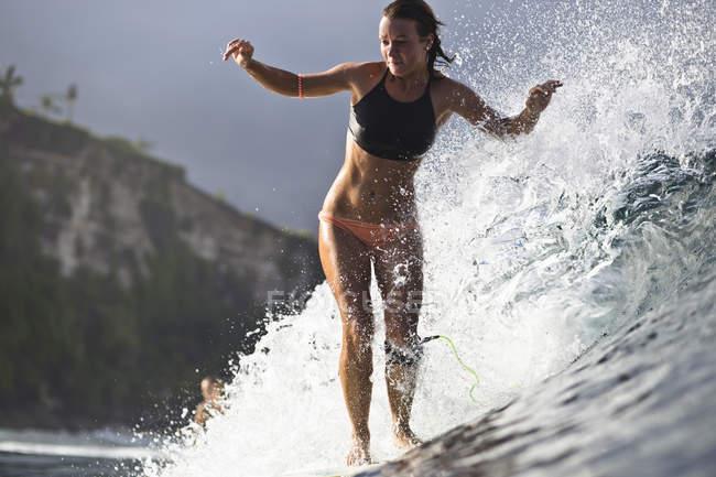 Индонезия, Бали, молодая спортсменка, занимающаяся серфингом в океане — стоковое фото