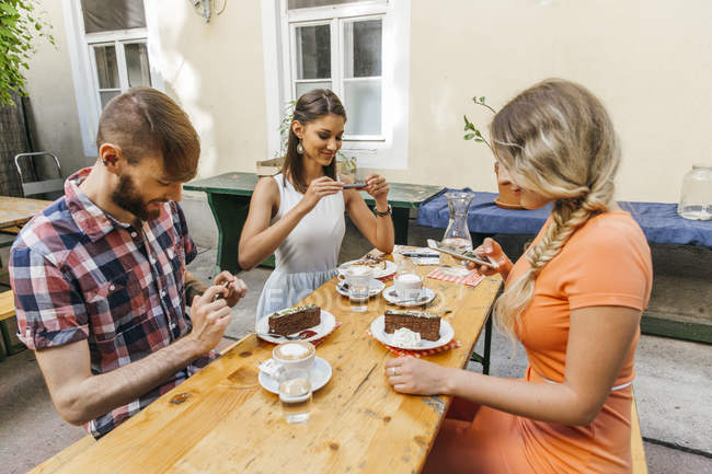 Friends sitting outdoors with coffee and cake taking cell phone pictures — Stock Photo