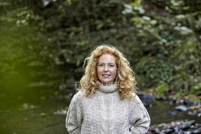 Retrato de mulher sorridente em pé na natureza — Fotografia de Stock