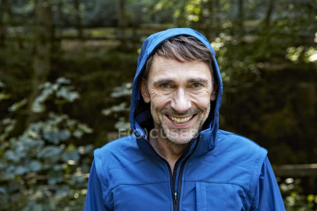 Portrait of smiling man wearing hooded jacket — Stock Photo