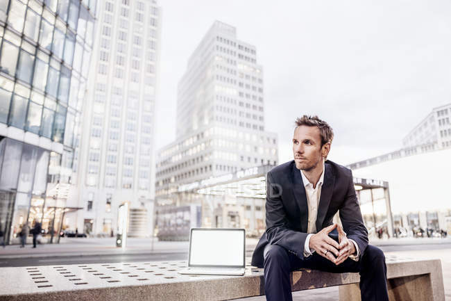 Businessman sitting on bench with laptop on Potsdamer Platz — Stock Photo
