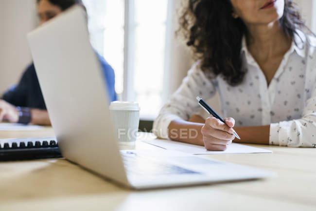 Femme d'affaires assise en réunion, prenant des notes avec un stylo à bille — Photo de stock