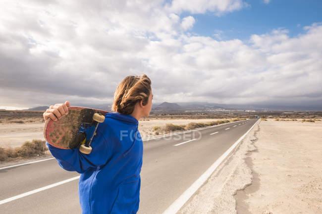 Espanha, Tenerife, menino com skate andando na estrada rural vazia e olhando para a distância — Fotografia de Stock