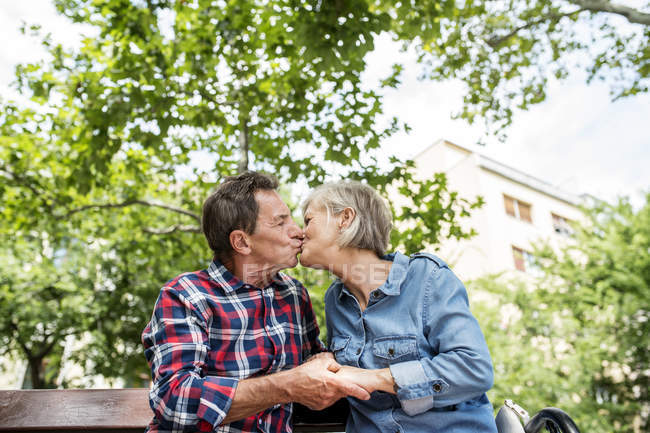 Happy cute senior couple sitting on bench and kissing at park — Stock Photo