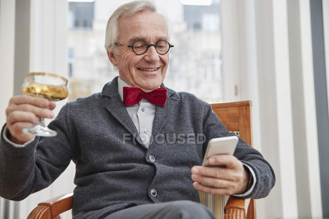 Smiling senior man with cell phone sitting on chair holding champagne glass — Stock Photo