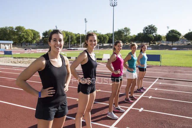 Coureuses souriantes debout sur la piste de tartan à la ligne de départ — Photo de stock