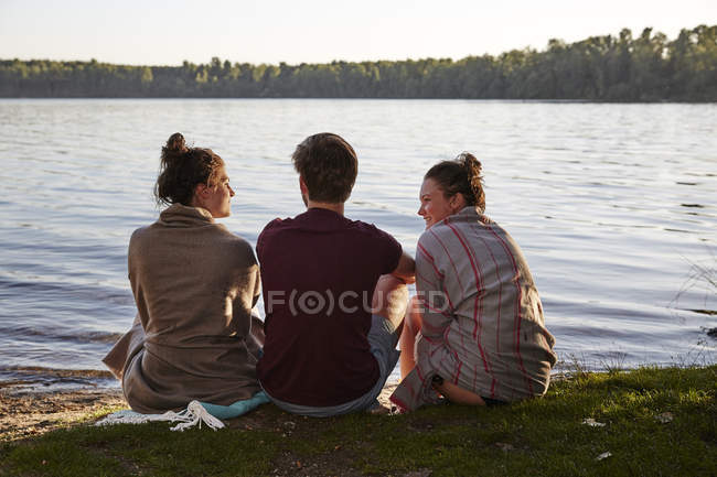 Friends sitting at a lake at sunset talking — Stock Photo