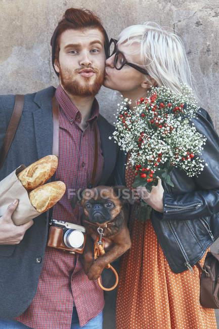 Молодая пара с мопсом целуется на улице — стоковое фото